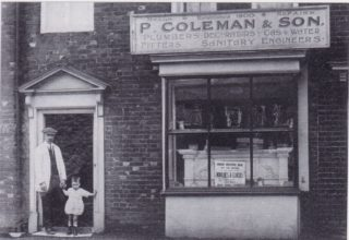 Percy Coleman and his grandson standing at the door of his shop in London End.
