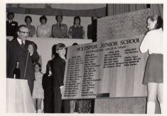 Black and white photograph of Mr Tame, head boy and head girl with plaque showing names since 1951.