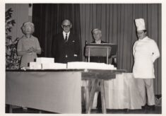 Black and white photograph of the celebration cake including headmaster and chef.