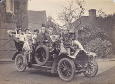 Black and white photograph of the cast of The Mikado, sitting on a car