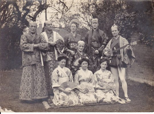 Black and white photograph showing the cast of The Mikado ; WFC Holden with mandolin   Unknown