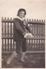 Black and white photograph of a man in costume in front of a fence, possibly from Patience