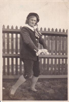 Black and white photograph of a man in costume in front of a fence | Unknown