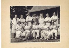 Oversized photograph mounted on beige card of the cricket pavilion and group of players
